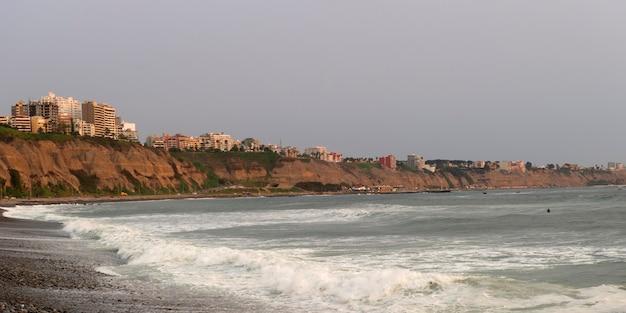 Wellen mit einer stadt im hintergrund, miraflores-bezirk, lima-provinz, peru