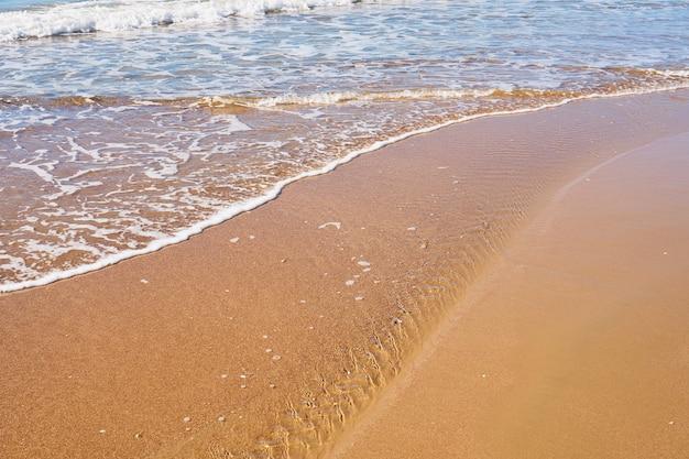 Wellen mit schaum an einem sandstrand.