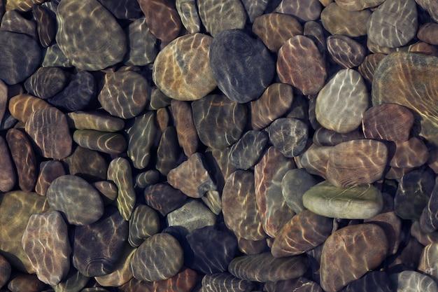 Wellen reflektieren licht auf seichtem wasser über kieselsteinen