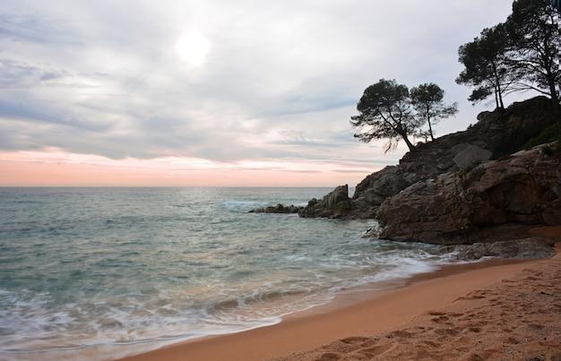 Wellen schlagen die felsen des meeres in einem sonnenaufgang in der costa brava