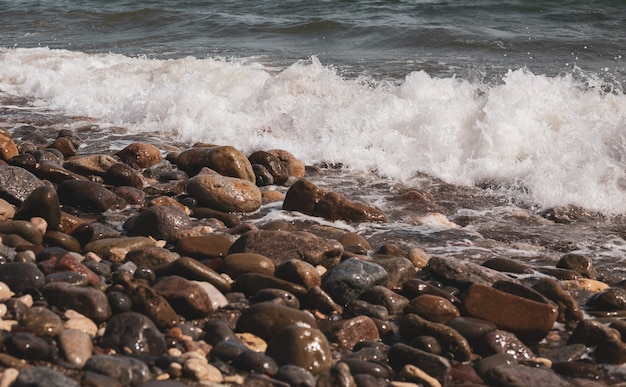 Wellen spritzen auf steinen an der küste. wellen der mittelmeerküste