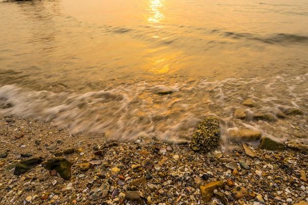 Wellen spülten bei sonnenuntergang mit ins ufer