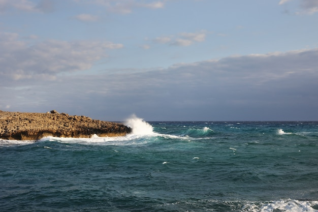 Wellen treffen die felsigen klippen an einem strand in zypern. dieses wetter mag für den wassersport gefährlich sein, aber gleichzeitig sind die wellen und ihre spritzer hübsch und wild