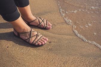 Wellen und nackte Füße an einem Sandstrand