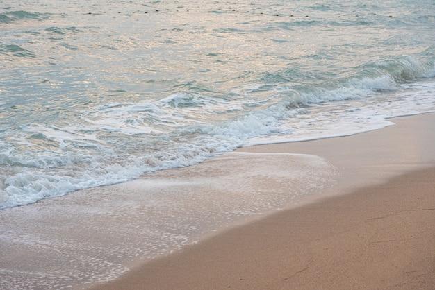 Wellen- und sandstrandhintergrund mit kopienraum.