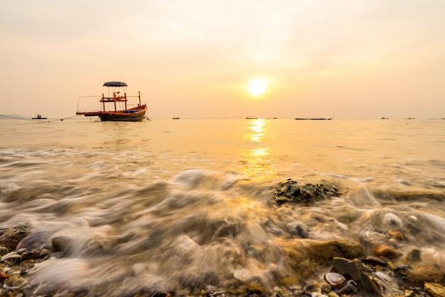 Wellen wuschen in das ufer im sonnenuntergang mit unschärfe des fischerboothintergrunds