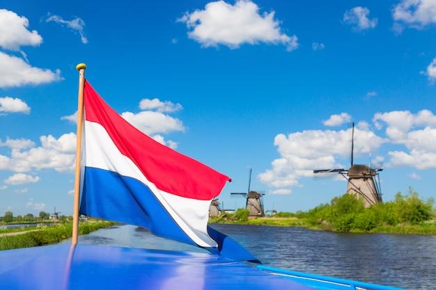 Wellenartig bewegende niederländische flagge auf einem kreuzschiff gegen berühmte windmühlen in kinderdijk-dorf in holland