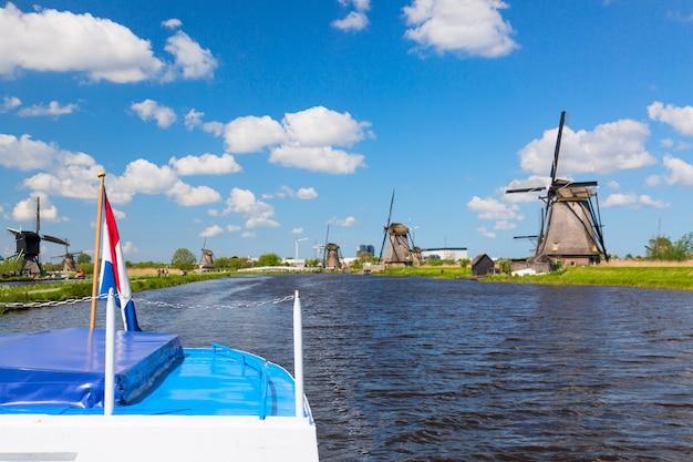 Wellenartig bewegende niederländische flagge auf einem kreuzschiff gegen berühmte windmühlen in kinderdijk-dorf in holland.