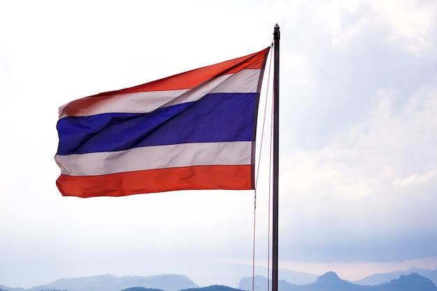Wellenartig bewegende thailändische flagge von thailand mit hintergrund des blauen himmels und des berges