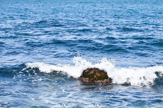 Wellenartig bewegende wasseroberfläche und stein des adriatischen meeres.