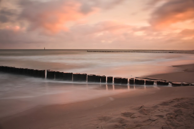 Wellenbrecher am sandstrand während des sonnenuntergangs