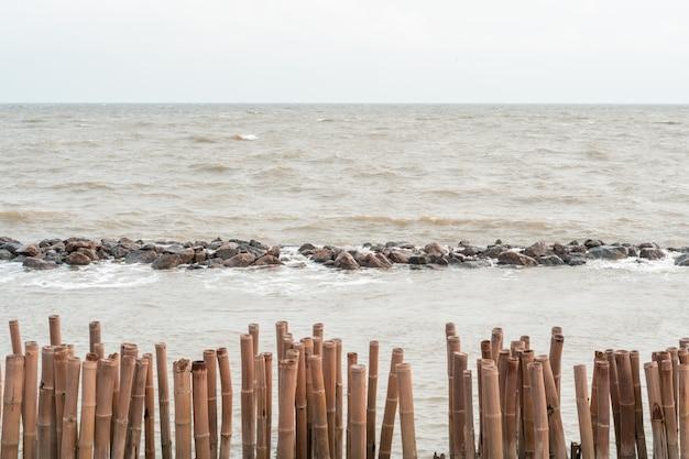 Wellenbrecherbambuspfosten und steinküstenschutz am bangkuntien-mangrovenwald setzen, seeseite thailand auf den strand