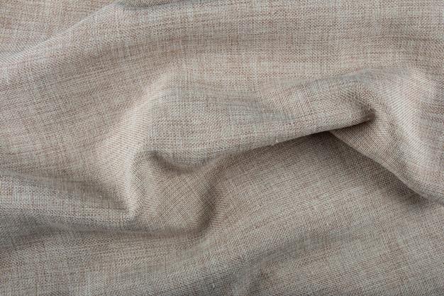 Wellenförmige beige stoffstruktur.