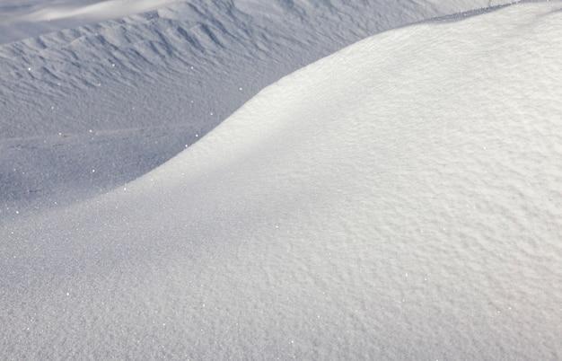 Wellenförmige und hügelige oberfläche von tiefschnee driftet in der wintersaison, schöne natur an einem frostigen morgen