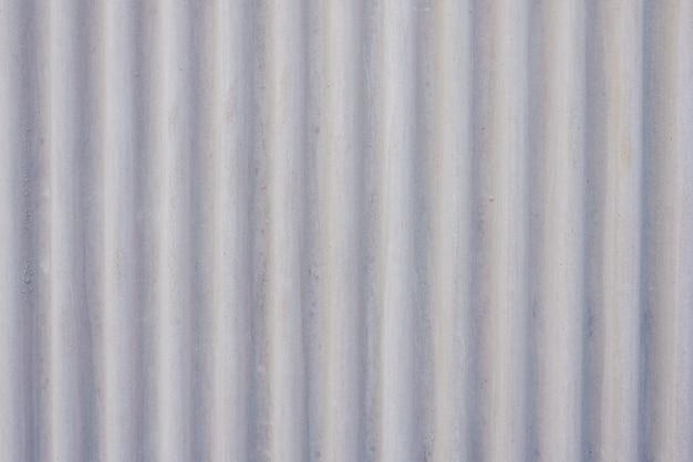 Wellenförmiger metallhintergrund auf einer grauen wand.