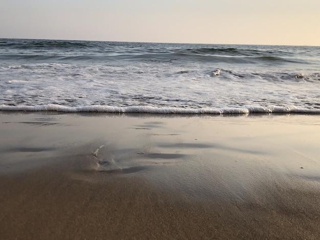 Wellenförmiger ozean, der auf den sandstrand trifft und unter dem bunten himmel glänzt
