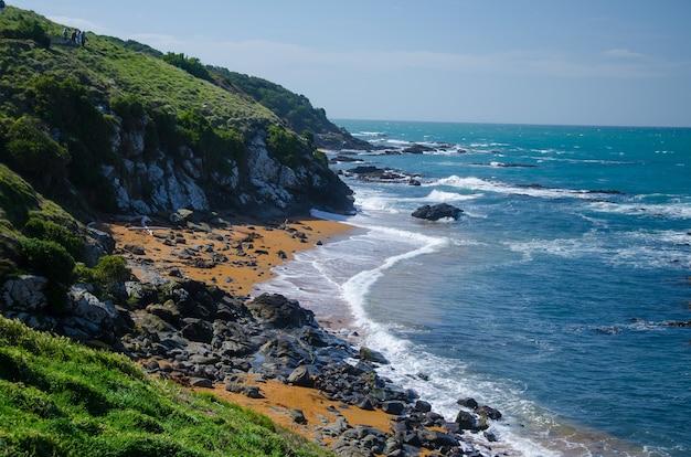 Wellenförmiger ozean, der den felsigen strand trifft, der durch klippen in neuseeland umgeben ist