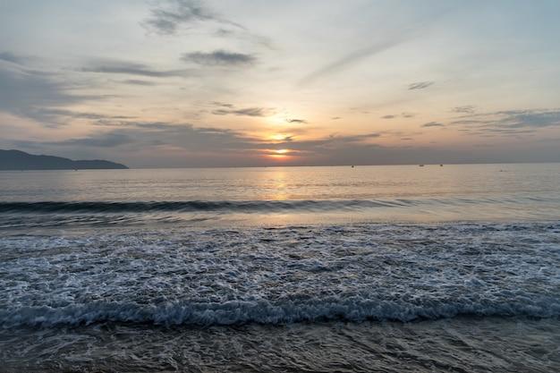 Wellenförmiger ozean und die untergehende sonne