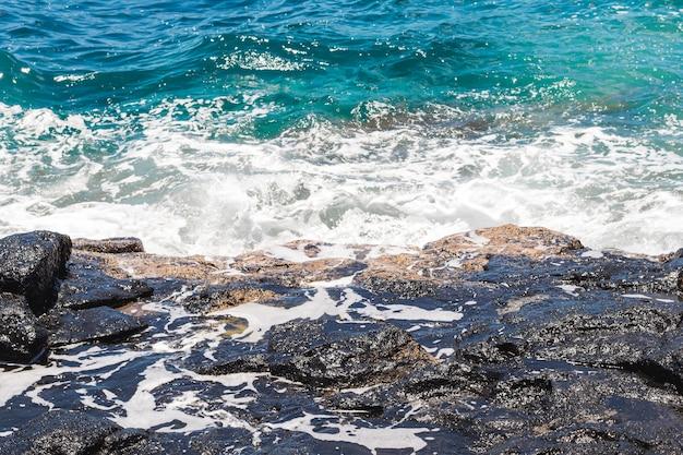 Wellenförmiges kristallines wasser der nahaufnahme an der küste