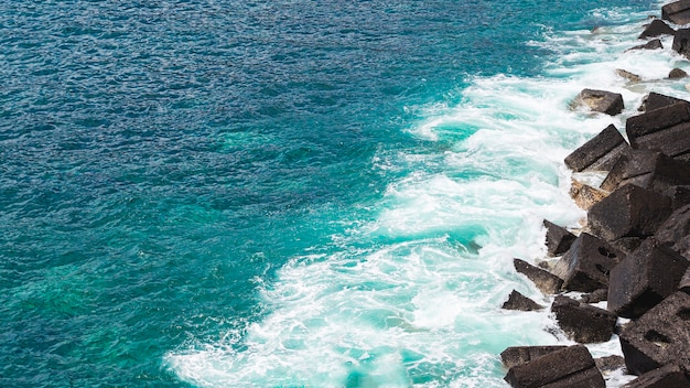 Wellenförmiges wasser der nahaufnahme an der felsigen küste