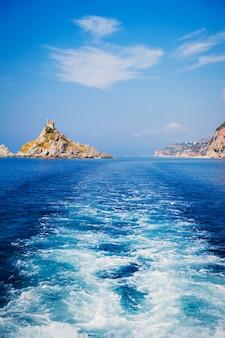 Wellenverfolgungsschwänze des schnellboots auf blauer wasseroberfläche im meer. blick auf graue felseninsel. budva riviera, montenegro