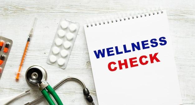 Wellness check steht in einem notizbuch auf einem weißen tisch neben pillen und einem stethoskop. medizinisches konzept