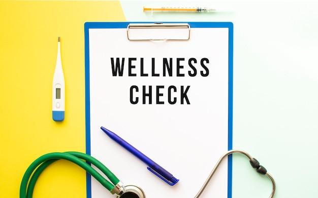 Wellness check text auf einem briefkopf in einem medizinischen ordner auf einem schönen hintergrund. stethoskop, thermometer und stift.