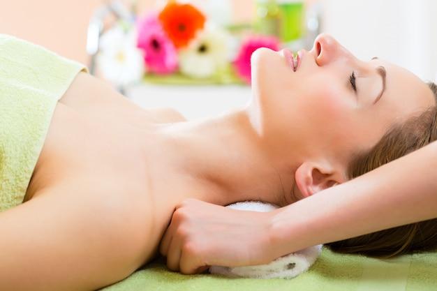 Wellness - frau bekommt schultermassage im spa