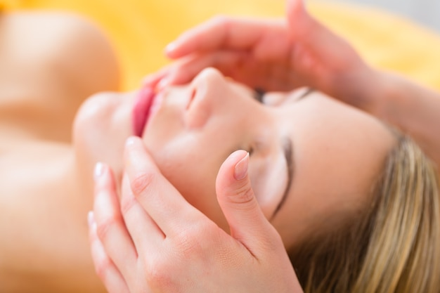 Wellness - frau, die kopf- oder gesichtsmassage im spa erhält