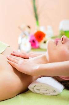 Wellness - frau, die schultermassage im badekurort erhält