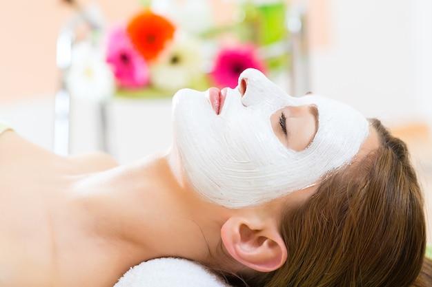 Wellness - frau erhält gesichtsmaske im spa für saubere und feuchte haut
