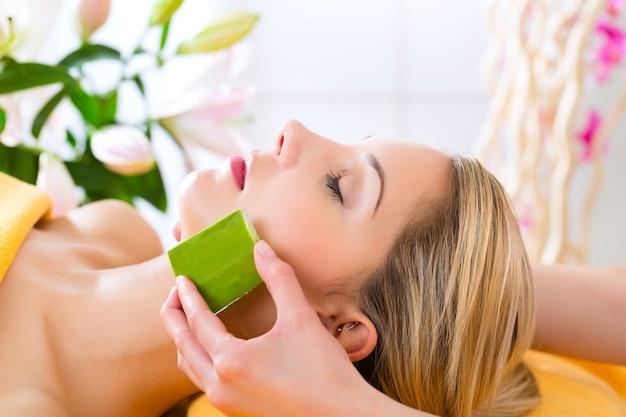 Wellness - frau erhält kopf- oder gesichtsmassage mit aloe vera im spa