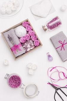 Wellness-geschenkbox mit lavendelblüten und lavendelaroma, badebombe, seife, meersalz, baderosen, baumwollgrauem handtuch