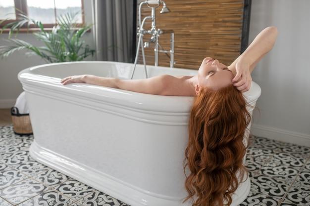 Wellness tag. schöne ingwerfrau, die in einem bad liegt und genossen schaut