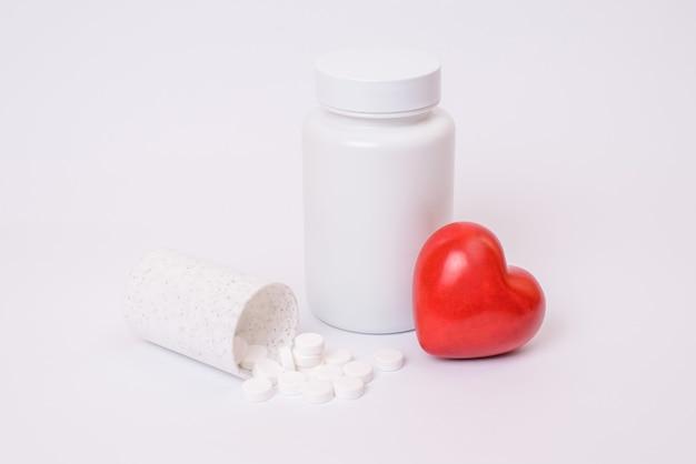 Wellness wohlbefinden vitalität schlaganfall klar klar klinik ungesundes konzept. schließen sie herauf foto von kleinen fall verschüttet tabletten auf tisch groß mit deckel rot hellem herzen isoliert kopierraum