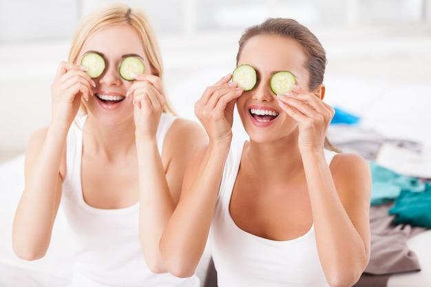Wellness zu hause. zwei schöne junge frauen, die gurkenstücke auf den augen halten und lächeln, während sie auf dem bett sitzen