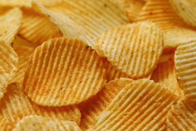 Wellpappe-kartoffelchips. lebensmittelhintergrund. draufsicht.