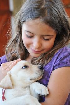 Welpen labrador retriever und kleines mädchen