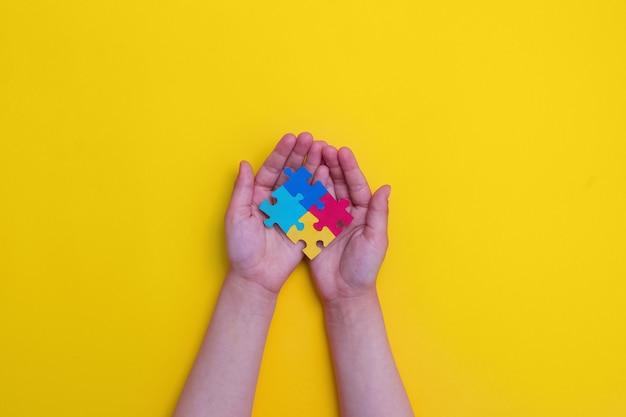 Welt-autismus-bewusstseinstag hände eines kleinen kindes, das bunte puzzles auf gelbem hintergrund hält