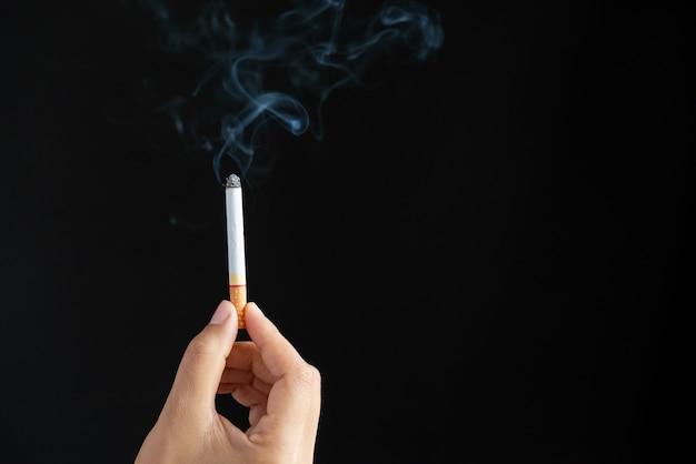 Welt kein tabak-tag, die hand des mannes, die zigaretten auf schwarzem hintergrund hält.