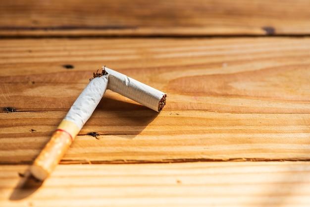 Welt kein tabak tag, nahaufnahme gebrochene zigarette auf holztisch hintergrund.