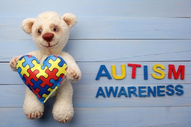 Weltautismus-bewusstseins-tag mit teddybär, der puzzle- oder puzzle-muster auf herz hält