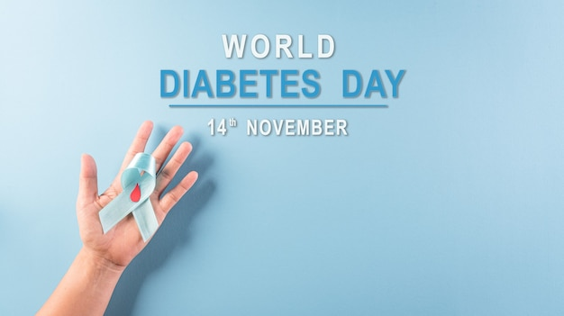 Weltdiabetes-tagesbewusstseinskonzept hand, die symbolische bogenfarbe des blauen bandes hält