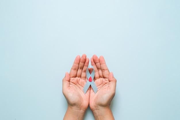 Weltdiabetestag und blaues bandbewusstsein mit rotem blutstropfen in den frauenhänden einzeln auf blauem hintergrund. weltdiabetestag, 14. november. platz kopieren. ansicht von oben