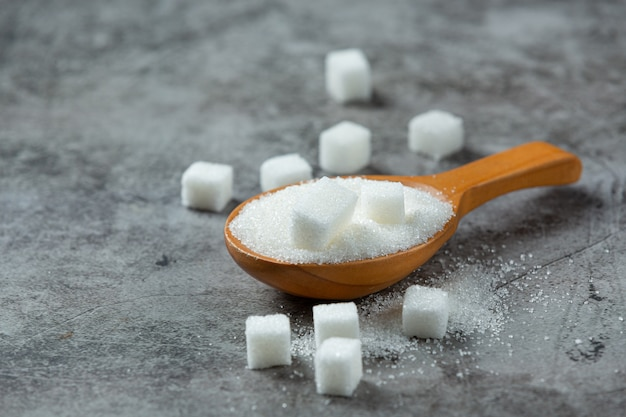 Weltdiabetestag; zucker in holzschale auf dunkler oberfläche