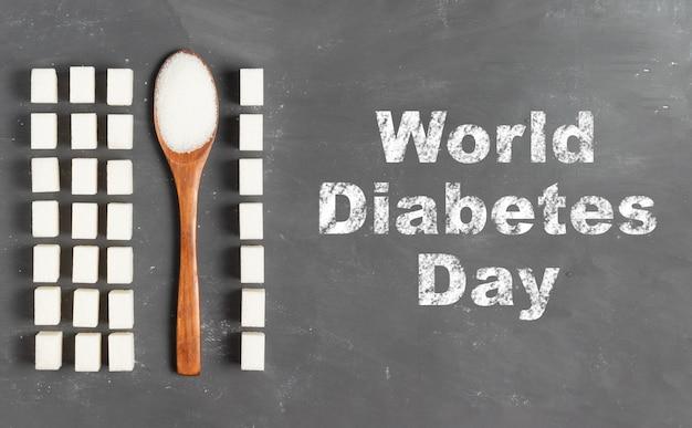 Weltdiabetestagbeschriftung in kreide auf grauem hintergrund mit zuckerklumpen