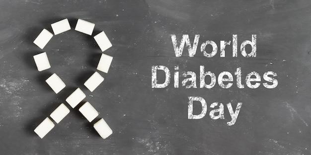 Weltdiabetestagbeschriftung in kreide auf grauem hintergrund mit zuckerwürfeln