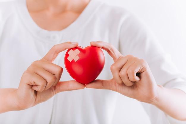 Weltgesundheitstag, gesundheitswesen und medizinisches konzept. frau, die rotes herz mit verband in den händen hält