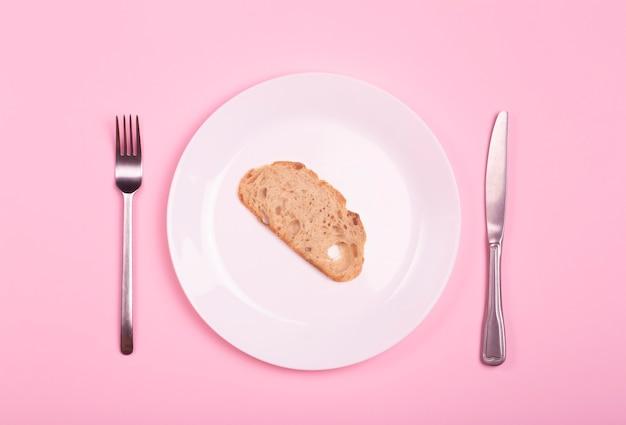 Welthunger- und armutskonzept. ein stück brot auf einem leeren teller auf einem rosa tisch.