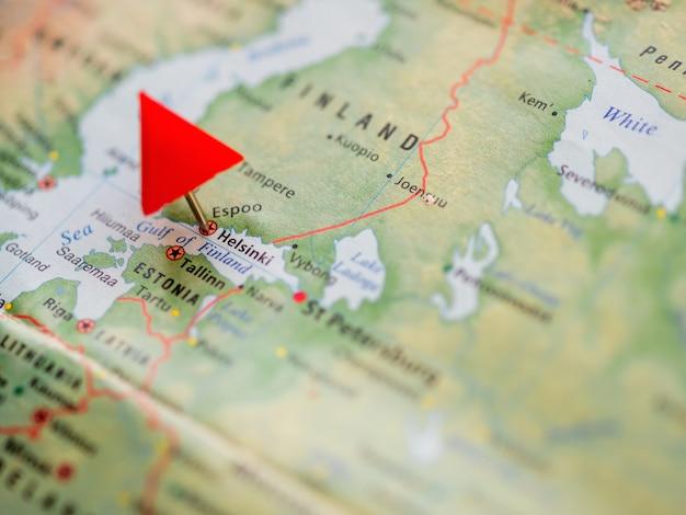 Weltkarte mit fokus auf finnland mit rotem dreieckstift von der hauptstadt helsinki.
